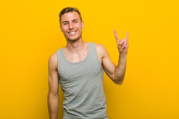 Jeune homme de sport caucasien montrant un geste de cornes comme un concept de révolution.
