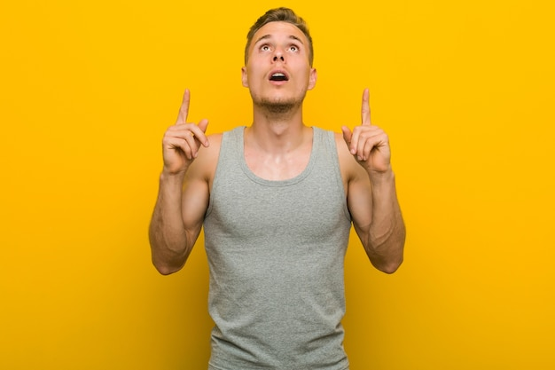 Jeune homme de sport caucasien pointant vers le haut avec la bouche ouverte.
