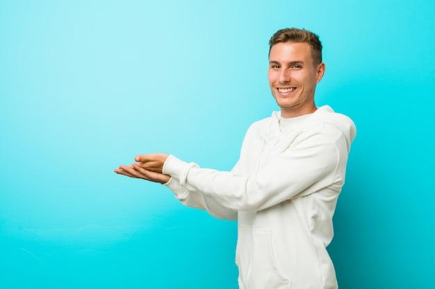 Jeune homme de sport caucasien tenant un espace vide sur une paume.
