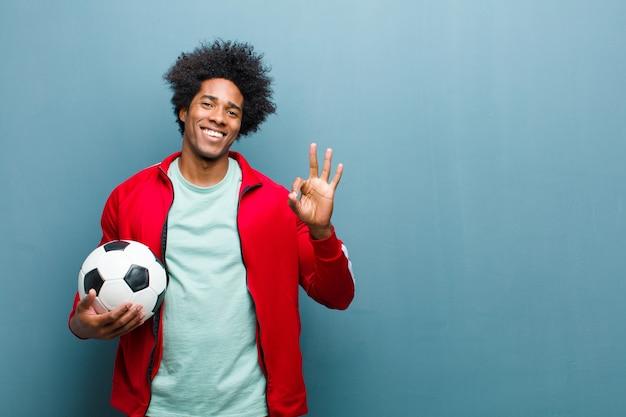 Jeune homme de sport noir avec un ballon de football contre grunge bleu wa