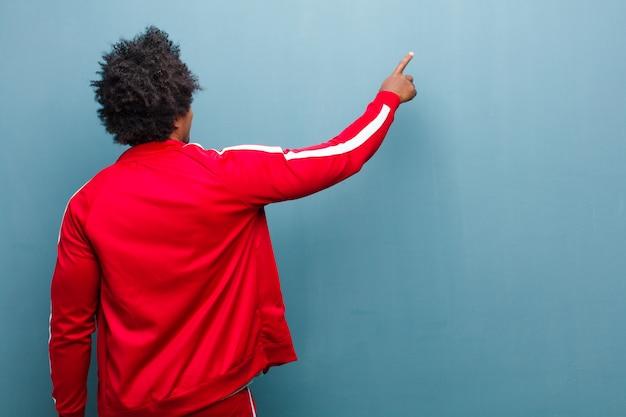Jeune homme de sport noir debout et pointant à l'objet sur l'espace de la copie, vue arrière contre le mur de grunge