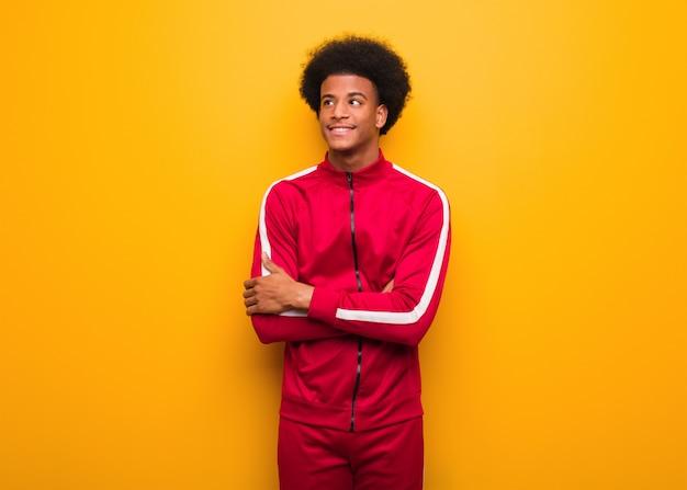 Jeune homme sport noir sur un mur orange souriant confiant et bras croisés, levant