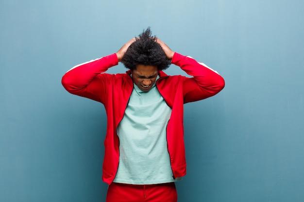Jeune homme de sport noir se sentant stressé et frustré, levant les mains sur son visage, fatigué, malheureux et souffrant de migraine contre mur