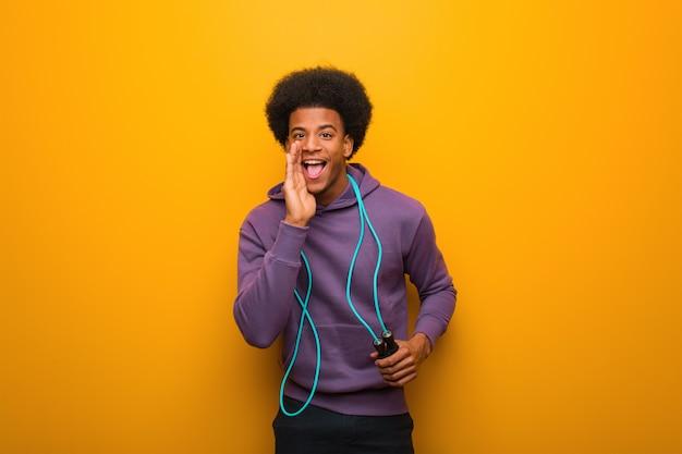 Jeune homme de sport noir tenant une corde à sauter criant quelque chose de joyeux à l'avant