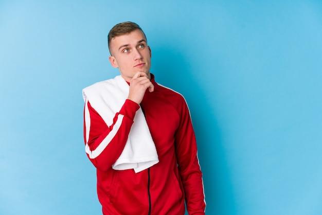 Jeune homme de sport à la recherche de côté avec une expression douteuse et sceptique.