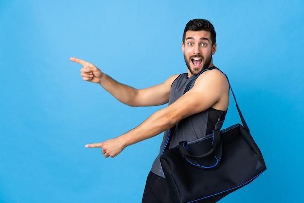 Jeune homme de sport avec sac de sport isolé sur le doigt pointé bleu sur le côté et présentant un produit