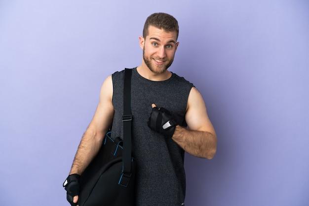 Jeune homme de sport avec sac de sport isolé sur un mur blanc avec une expression faciale surprise