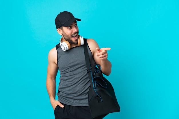 Jeune homme de sport avec sac de sport isolé sur le mur bleu, pointant le doigt sur le côté et présentant un produit