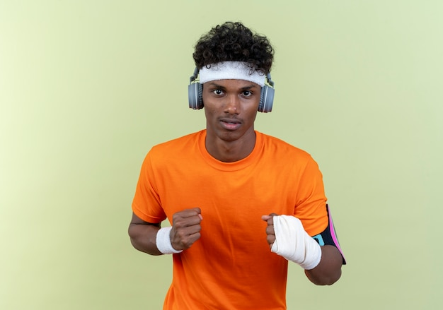 Jeune homme sportif afro-américain portant bandeau et bracelet et brassard de téléphone avec des écouteurs debout dans la pose de combat isolé sur mur vert