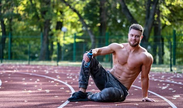 Jeune homme sportif assis sur une piste de course et au repos après un entraînement intensif sur un stade
