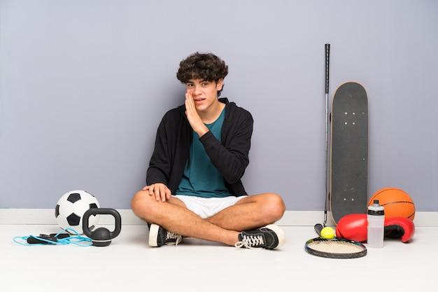 Jeune homme sportif assis sur le sol autour de nombreux éléments de sport chuchotant quelque chose