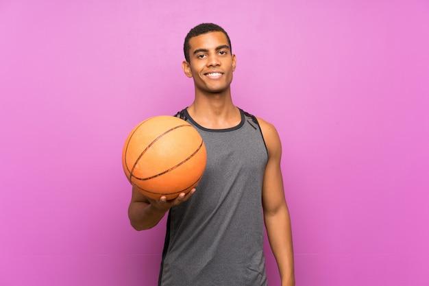 Jeune homme sportif avec une balle de basket souriant