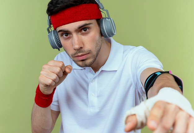 Jeune homme sportif en bandeau avec casque et brassard smartphone posant comme un combattant avec le poing fermé sur vert