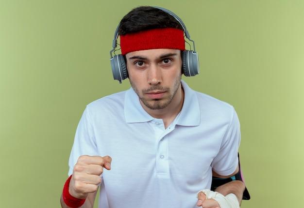 Jeune homme sportif en bandeau avec casque et brassard smartphone serrant le poing avec visage sérieux sur vert