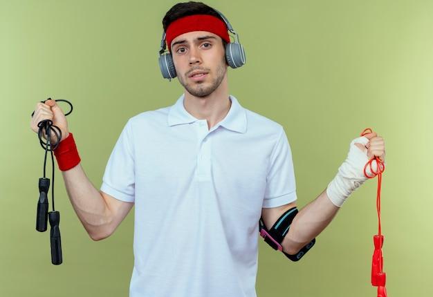 Jeune homme sportif en bandeau avec casque et brassard smartphone tenant deux cordes à sauter confus sur vert