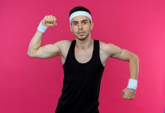 Jeune homme sportif en bandeau posant comme athlète levant le poing montrant les biceps sur rose