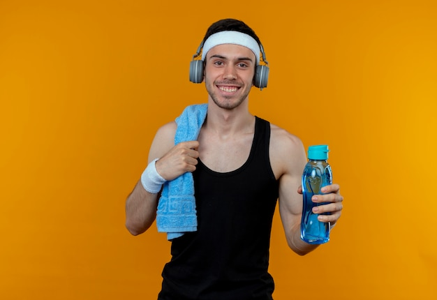 Jeune homme sportif en bandeau avec une serviette sur l'épaule tenant une bouteille d'eau regardant la caméra en souriant debout sur fond orange
