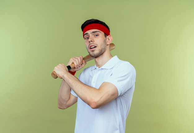 Jeune homme sportif en bandeau tenant une batte de baseball avec une expression sérieuse confiante debout sur un mur vert