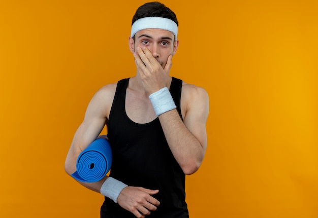 Jeune homme sportif en bandeau tenant un tapis de yoga couvrant la bouche avec la main étant choqué debout sur un mur orange