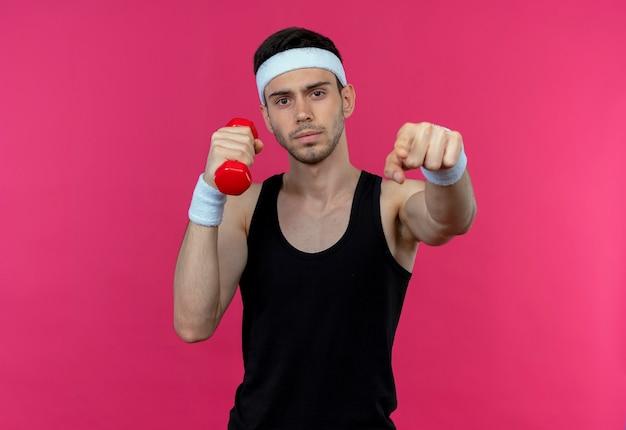 Jeune homme sportif en bandeau travaillant avec haltère pointant avec le doigt avec un visage sérieux debout sur un mur rose