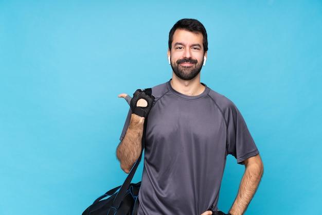 Jeune homme sportif avec barbe sur fond bleu isolé pointant sur le côté pour présenter un produit