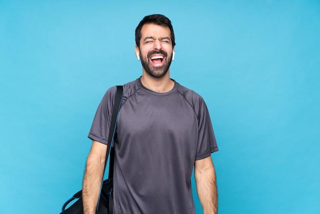 Jeune homme sportif avec barbe sur mur bleu isolé, criant à l'avant avec la bouche grande ouverte