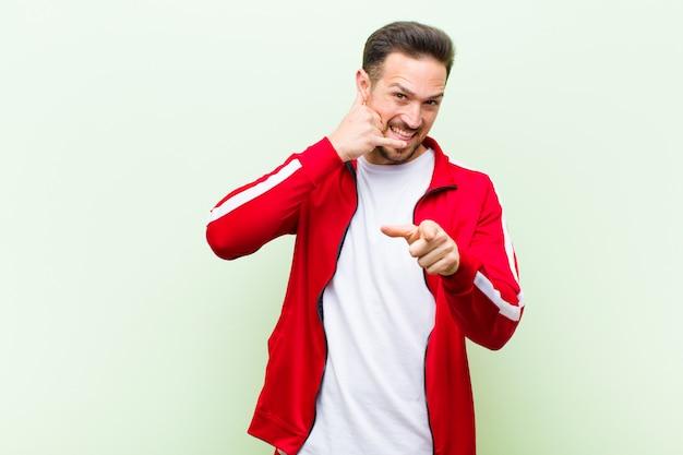 Jeune homme sportif beau ou moniteur souriant joyeusement et pointant à la caméra