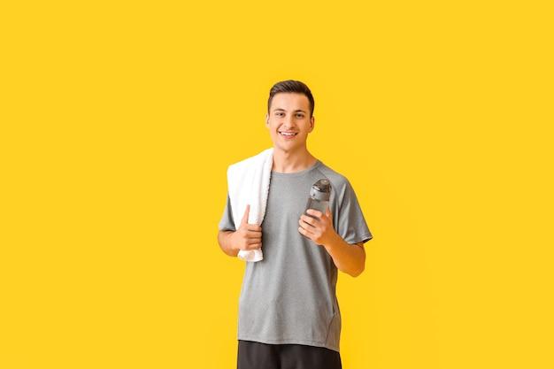 Jeune homme sportif avec une bouteille d'eau sur fond de couleur