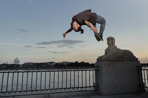 Jeune homme sportif faisant backflip en ville
