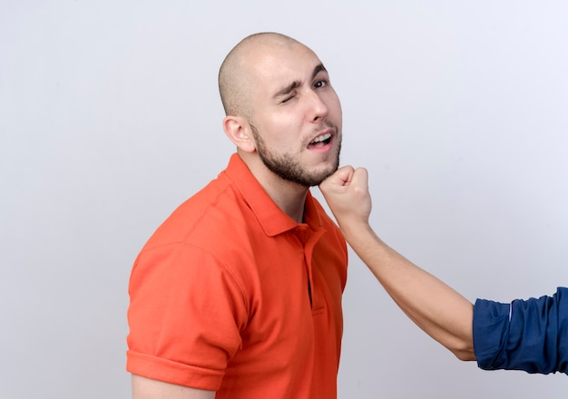 Jeune homme sportif frappé par quelqu'un isolé sur un mur blanc