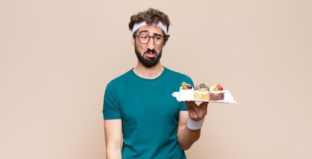 Jeune homme sportif avec des gâteaux sur un mur plat