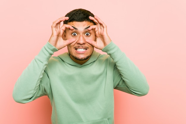 Jeune homme sportif hispanique, gardant les yeux ouverts pour trouver une occasion de réussir.