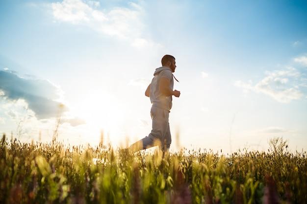 Jeune homme sportif jogging dans le champ au lever du soleil.