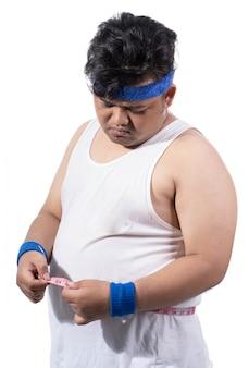 Jeune homme sportif mesurer son estomac