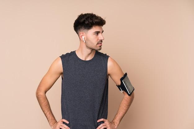 Jeune homme sportif sur mur isolé, posant avec les bras à la hanche et à la recherche de côté