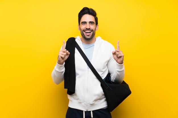 Jeune homme sportif sur un mur jaune isolé pointant vers le haut une excellente idée
