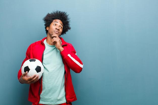 Jeune homme sportif noir avec un ballon de football contre le mur bleu grunge