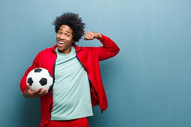 Jeune homme sportif noir avec un ballon de football contre wa bleu grunge