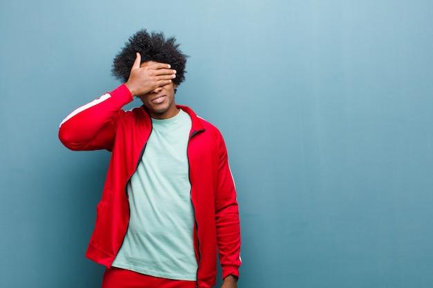 Jeune homme sportif noir couvrant les yeux d'une main, effrayé ou anxieux, se demandant ou aveuglément attendant une surprise contre le mur de grunge