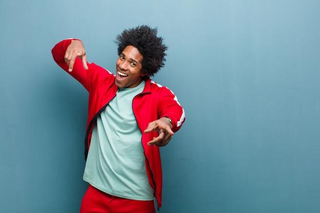 Jeune homme sportif noir se sentant heureux et confiant, pointant vers la caméra à deux mains et riant, vous choisissant contre grunge