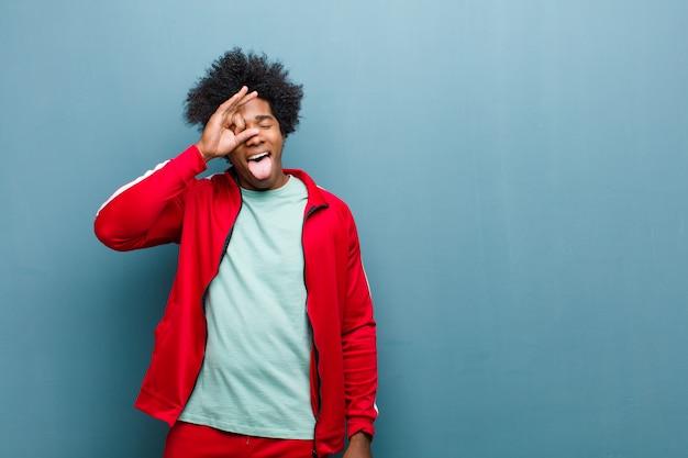 Jeune homme sportif noir souriant joyeusement avec grimace, plaisantant et regardant à travers un judas, espionnant des secrets