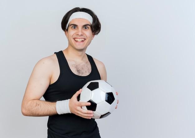 Jeune homme sportif portant des vêtements de sport et un bandeau tenant un ballon de football à l'avant souriant avec un visage heureux debout sur un mur blanc