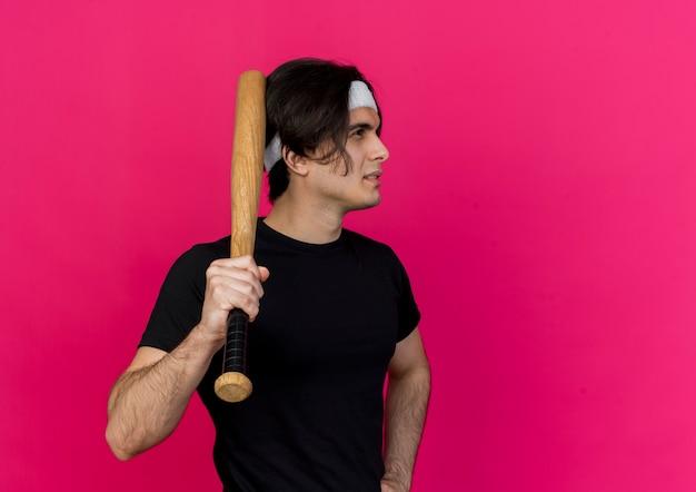 Jeune homme sportif portant des vêtements de sport et bandeau tenant une batte de baseball à côté avec un visage sérieux