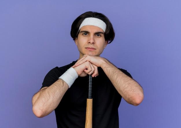 Jeune homme sportif portant des vêtements de sport et bandeau tenant une batte de baseball avec un visage sérieux