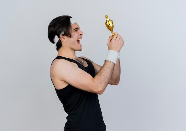 Jeune homme sportif portant des vêtements de sport et un bandeau tenant le trophée en le regardant heureux et excité debout sur un mur blanc