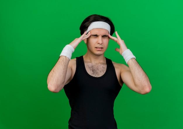 Jeune homme sportif portant des vêtements de sport et un bandeau touchant ses tempes souffrant de maux de tête