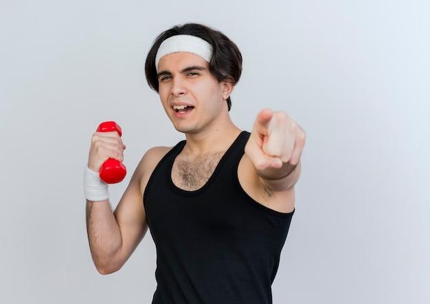 Jeune homme sportif portant des vêtements de sport et un bandeau travaillant avec haltère pointant avec l'index à l'avant souriant joyeusement debout sur un mur blanc