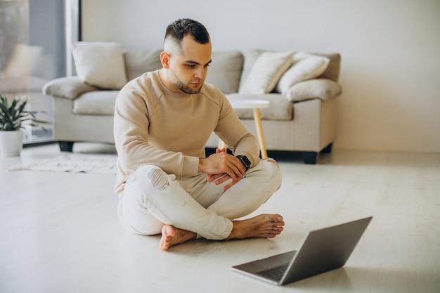 Jeune homme sportif pratiquant le yoga à la maison