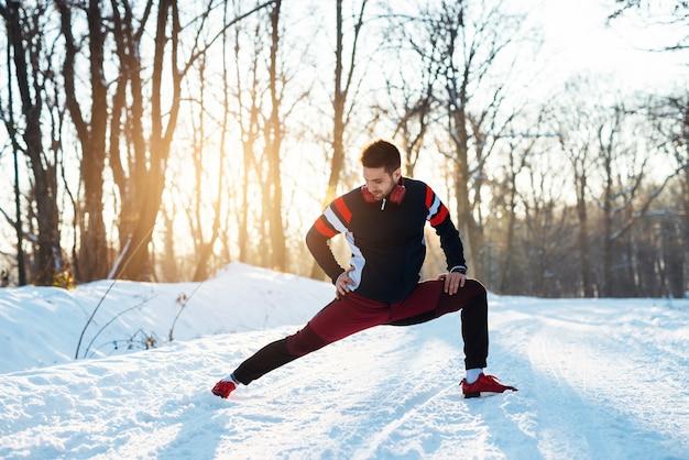 Jeune homme sportif qui s'étend de la jambe et se réchauffe avec des écouteurs sur la route d'hiver couverte de neige.