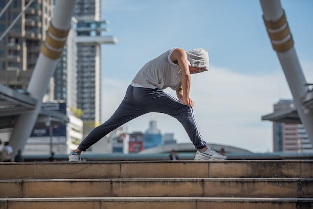 Jeune homme sportif qui s'étend de jambes sur la ville moderne, mode de vie sain le matin tous les jours.